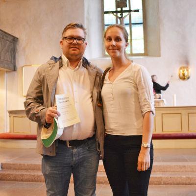En man och en kvinna står bredvid varandra framför altaret i Borgå domkyrka. De tittar in i kameran.