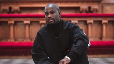 Rapparen PastoriPike sitter framför en altare i kyrkan.