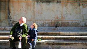 Pappa ja poika istuvat portailla