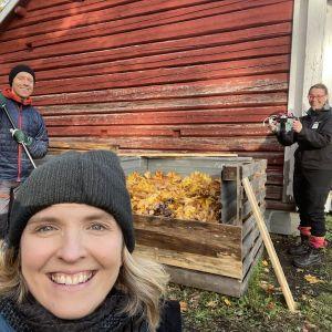 Kolme henkilöä ulkona kompostin äärellä.