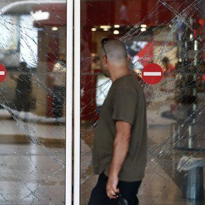 Mies käveli rikkoutuneiden lasiovien ohitse Atatürkin lentokentällä.