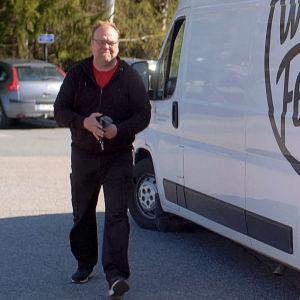Benjamin Laustiola står framför en vit skåpbil.