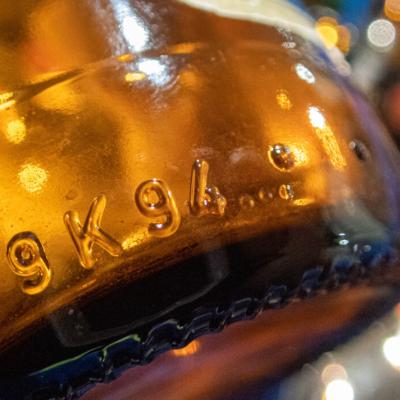 Ruskea lasipullo, pullon pohjassa kirjaimia.