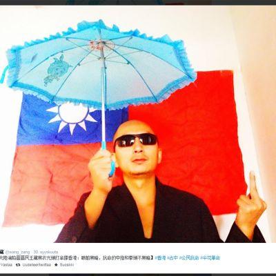 Wang Chang sateenvarjon kanssa, keskisormi pystyssä.