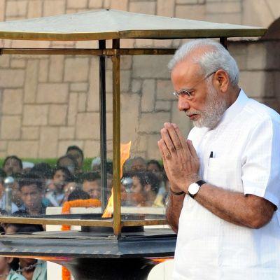 Valkoiseen paitaan pukeutunut mies on kädet vastakkain rinnan edessä, hänen vieressään suuri lasein suojattu liekki.