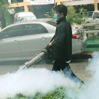 Terveysviranomainen kantaa hyttysten torjuntamyrkkyä suihkuttavaa ruiskua Bangkokin kadulla. Kemikaalia näkyy ilmassa.