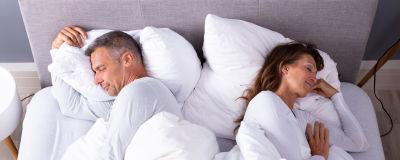 man och kvinna sover med ryggarna mot varandra, både belåtet leende