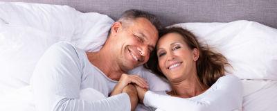 Leende man och kvinna ligger i en säng