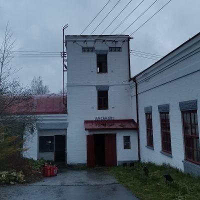 Vaalea ja matala voimalaitosrakennus.