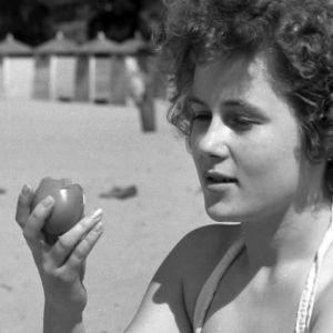 Tyttö ottaa rannalla aurinkoa toimatti kädessä
