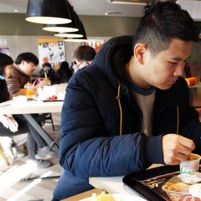 Mies syö pikaruoka-ateriaa.