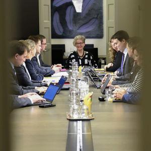 Parterna i poststrejken sitter kring ett bord och förhandlar.
