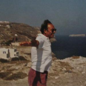 Leveästi hymyilevä italialaismies aurinkolaseissaan ja shortsiasussaan seisoo päivänpaisteessa rantakallioilla. Hän on levittänyt kätensä kuin lentoasentoon, taustalla näkyy yksinkertaisia kivitaloja ja merta sekä suuri laiva horisontissa.