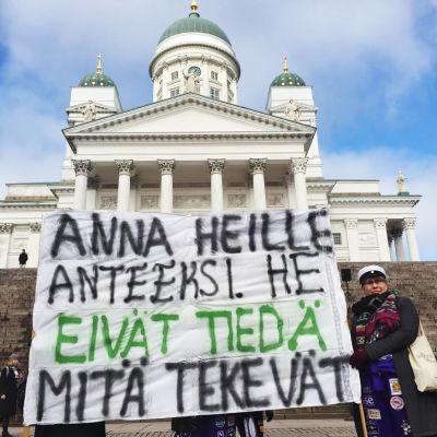 """Mielenosoittaja pitelee banderollia, jossa lukee """"Anna heille anteeksi. He eivät tiedä mitä tekevät."""""""