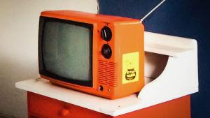 Oranssi matkatelevisio lähikuvassa, sivussa keltainen tarra, jossa teksti Rytmipuuroa.