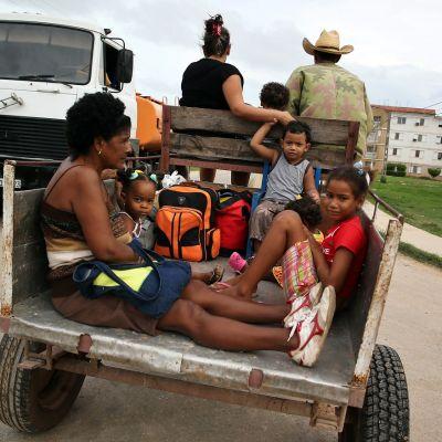 Nainen ja kolme lasta istuvat reppujen kanssa peräkärryssä, etuistuimella mies, nainen ja lapsi.