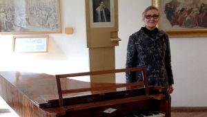 Toimittaja Paula Nurmentaus Franz Schubertin flygelin mutkassa.