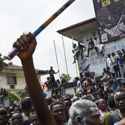 mies väkijoukon edessä voitonmerkkejä käsissään