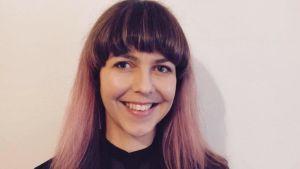 Porträtt av skribenten Salla med lila hår och leende.