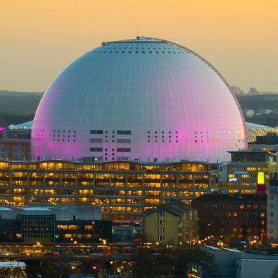 Arenan Globen i Stockholm, upplyst med ett rosa sken.