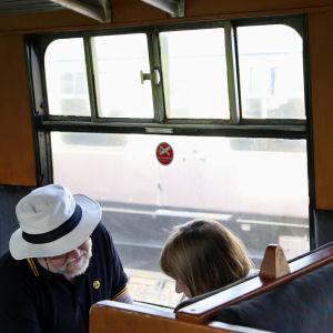 Ett par sitter i en gammal tågkupée.