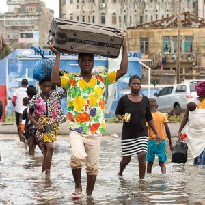 Människor går på översvämmad gata i Moçambique.