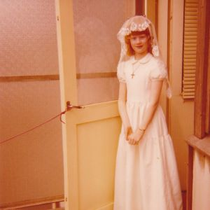 Lilli Earl nuorena valkoisessa, pitkässä puvussa, pitsihuivi päässä, suuri ristiriipus kaulassa