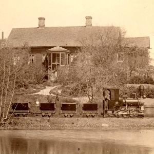 Ångloket Lill-Bässen drar kolvagnar längs Åkerraden på Fiskars bruk på 1890-talet. I bakgrunden står huset Fagerbo.