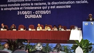 Kofi Annan håller ett tal bredvid en panel.