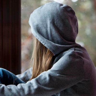 Barn i grå luvtröja tittar ut genom fönstret.