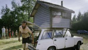 Man invid sin Ladabil med en liten bastu på taket