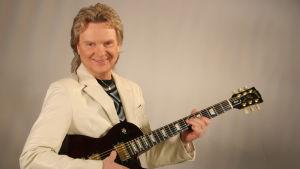 En äldre glad musiker med en elgitarr i handen, vit kavaj.