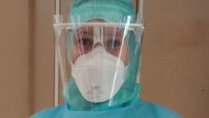 En läkare i full skyddsutrustning med andningsmask, plastvisir och skyddsdräkt.