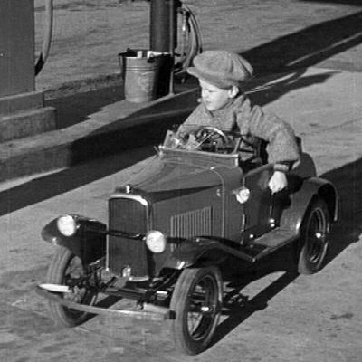 Pieni poika istuu vanhanmallisessa polkuautossa.