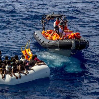 En gummibåt med flyktingar nås av en annan gummibåt med räddningsmanskap som kastar flytvästar till flyktingarna.