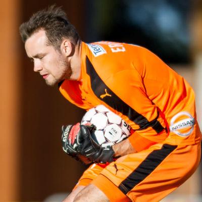 Carljohan Eriksson i orangefärgad speltröja räddar ett skott.