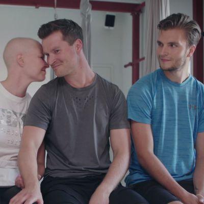 Pariskuntaystävykset istuvat joogasalissa penkillä ja katsovat hymyillen toisiinsa.