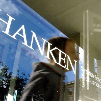 Glasdörr med Svenska handelshögskolans logo och reflektionen av en elev