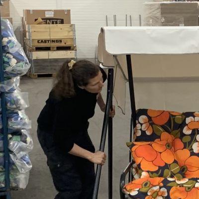 En man och en kvinna monterar en trädgårdsgunga i en lagerlokal.