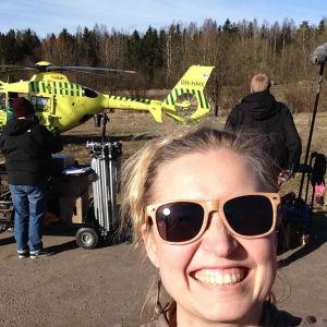 Hanna Isola etualalla, taustalla lääkärihelikopteri ja Syke-sarjan kuvaustiimiä.