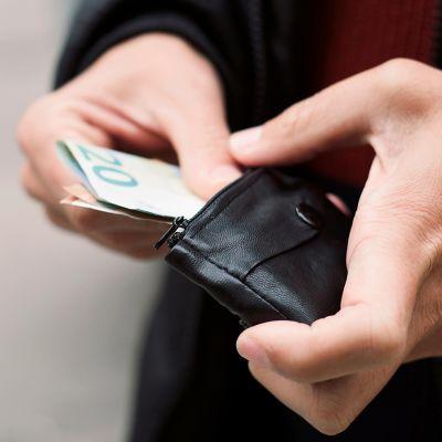 Mies laittaa seteliä lompakkoon.