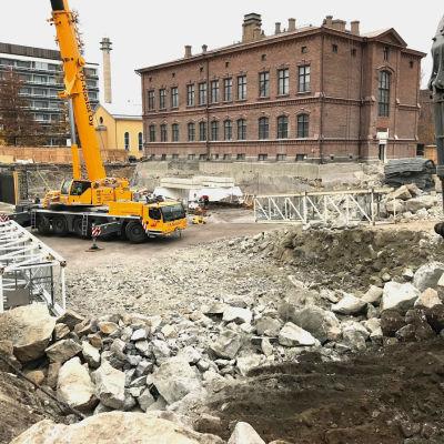 Bilden föreställer byggnadsarbetet vid flickiskvarteret i Vasa. En lyftkran och en grävskopa kan skymtas