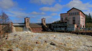 Vattenkraftverk med en damm i en kraftig fors.