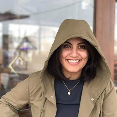 Kvinna med mörkt hår och rockens huva på huvudet.