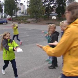 Johanna Pipping-Arrakoski hjälper Hanna Indrenius-Zalewski som deltar på en modersmålslektions utomhus.