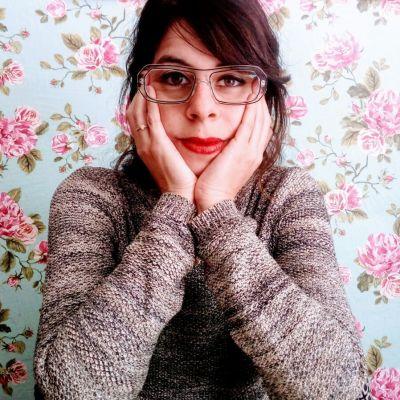 Sociologen Orna Donath framför en blommig tapet