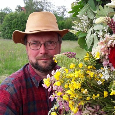 en man i hatt och rutig skjorta håller i en stor blombukett av vilda blommor i en blomsteräng