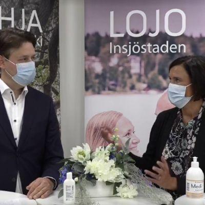 En man i kostym och en kvinna i mörka kläder ser på varandra där de står vid ett bord. Båda har munskydd och i bakgrunden finns affischer med texterna Lojo-Lohja.