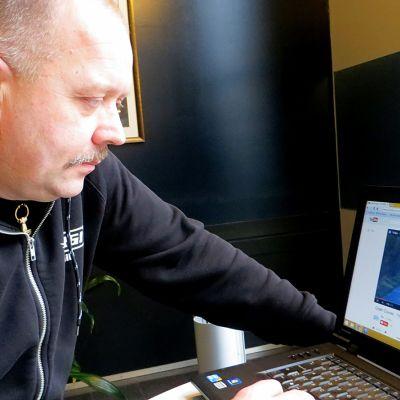 Mies katsoo tietokoneelta videota
