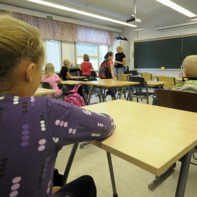 Lapsia istumassa pulpettien äärellä luokkahuoneessa.